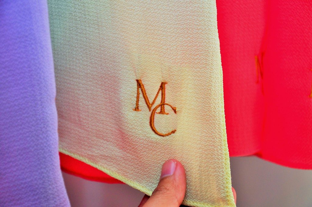 Headscarves that are monogrammed with the initials of the company, one of the many pieces offered by the local company.